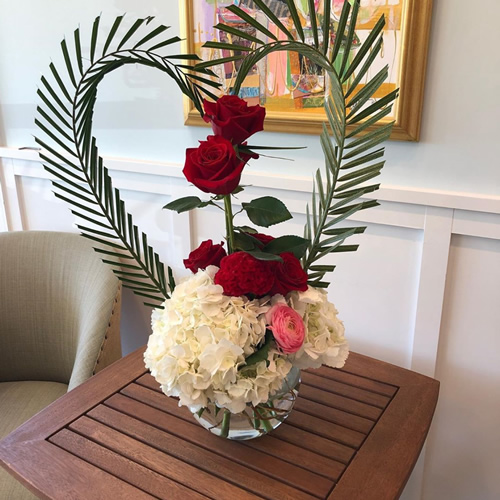 Flower arrangement with roses and palms shaped into heart